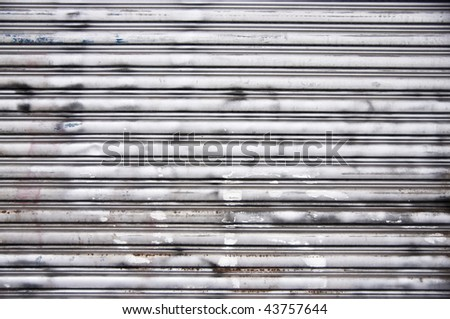 A nice steel garage door background texture. Complete with rust spots, spray paint, scratches and dings. - stock photo