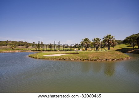 A nice view of a golf course with a lake and blue sky. - stock photo