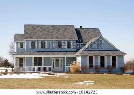 A nice winter photo of a house with blue siding