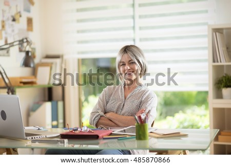 a nice 40 year old woman , she is sitting at her desk, she is doing her accounts and she needs glasses  because she is presbyopic. she is relaxed, she is laughing