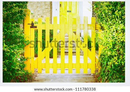 A nice yellow garden gate in front of an english house
