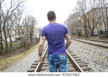 A nice young man portrait on the railroad - stock photo