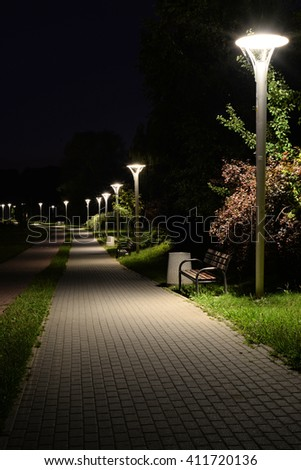 A Night in the Park. Late Autumn Night in the Park. Wood Benches and Park Alley.  - stock photo