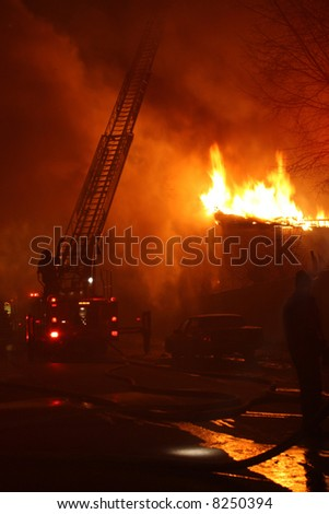 A night inferno seen from behind the firetruck - stock photo