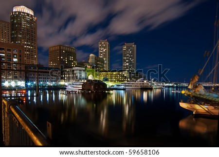 A night shot of the Boston inner harbor looking back towards downtown. - stock photo