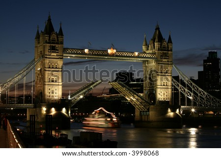 a night shot of tower bridge with the bridge raised and a boat passing under