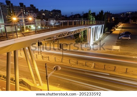 A night view of the seaside bridge  in Limassol, Cyprus. A view of the street, the wooden and glass pedestrian bridge