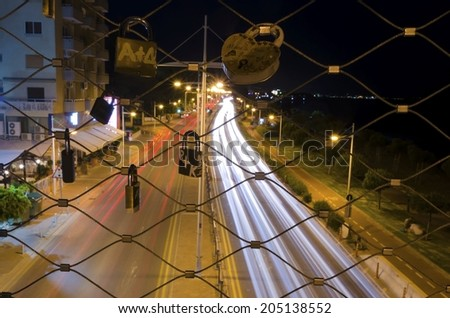A night view of the seaside pedestrian bridge connecting the beach to GSO Sports park in Limassol, Cyprus. A view of the cable that lovers hang padlocks, the traffic on the street and the sea. - stock photo