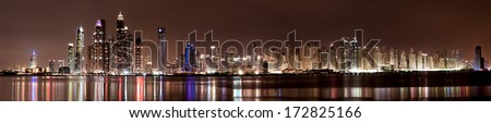 A nighttime  panoramic stitch of images looking from the Palm Jumeriah in Dubai, UAE across the Arabian Gulf at the Jumeriah Beach Residences and Dubai Marina - stock photo