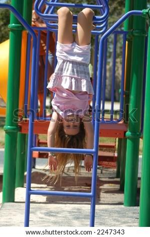 A nine year old girl upside down on monkey bars. - stock photo
