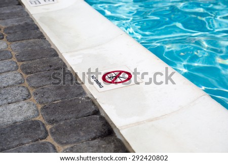 A no diving sign on the edge of a swimming pool - stock photo