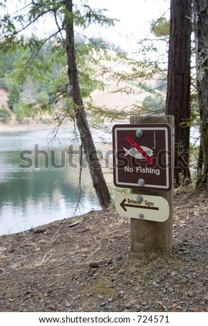 "A ""no fishing"" sign near a mountain lake. - stock photo"