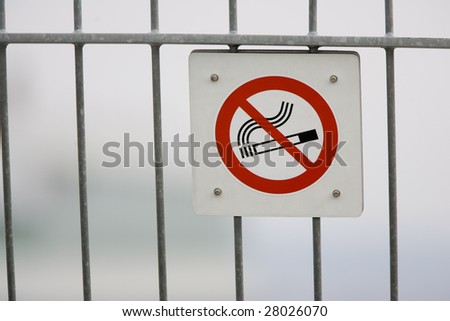 A no smoking sign posted on a fence. - stock photo