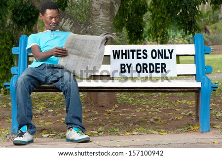 A non-white man sits on a bench in a park reserved for whites. This was commonplace during the apartheid years in South Africa. - stock photo
