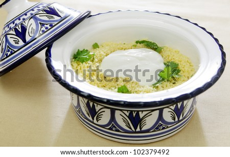 A north African pottery tagine bowl full of couscous, topped with fresh yoghurt and garnished with coriander leaves - stock photo
