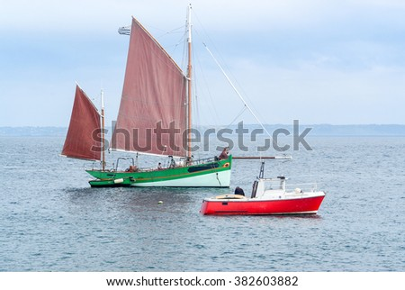 a nostalgic sailboat and a small motor boat in Brittany, France