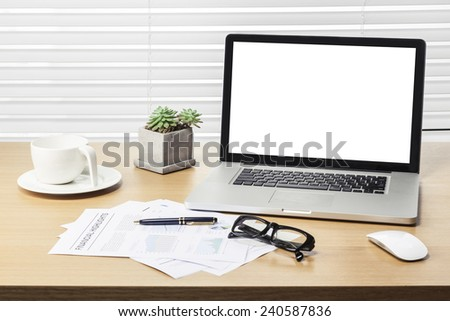 A note book, laptop, glasses, mouse, vintage compass, coffee cup, pen, graph paper(document) on the office desk(table) behind white blind. - stock photo