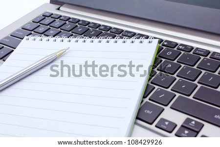a notebook and pen lie on the keyboard of computer