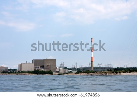 A nuclear power plant with large smoke stack and high power lines. - stock photo