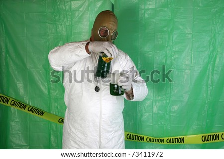 "A Nuclear Scientist or Chemical Engineer wears a white Hazmat Suit, Gas Mask, and Gloves as he mixes dangerous chemicals together while in a temperary plastic wrapped ""Safety Zone"" in a Disaster area - stock photo"