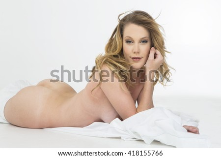 A nude figure model posing in a studio environment - stock photo