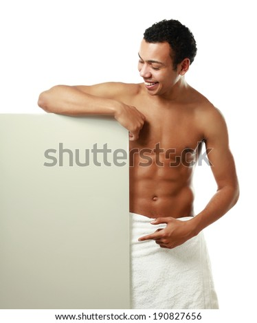A nude young man covering himself with a towel and standing near blank - stock photo
