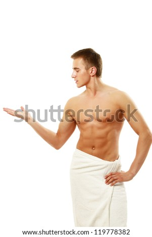 A nude young man covering himself with a towel, isolated on white background