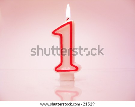 A number 1 candle lit against pink background. - stock photo