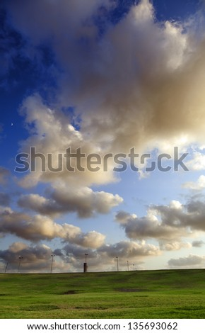 A number of street lights set in a row on a grassy hill at a park, beneath the dramatic cloudy afternoon sky. - stock photo