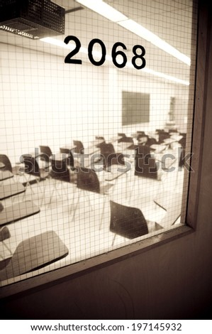 A numbered door stands before an empty classroom. - stock photo