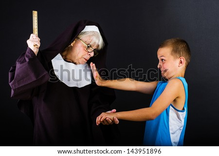 A nun threatening a boy with a ruler