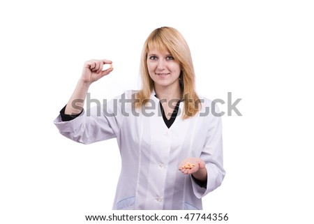 A nurse holds a small orange pill in her fingers. Female pharmacist is holding tablets. Woman  health care professional with a prescription. - stock photo