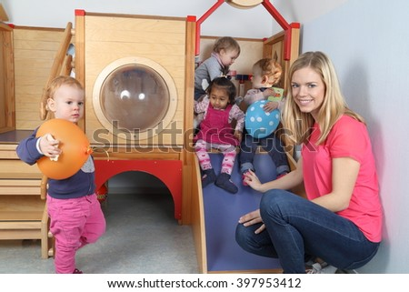 A Nursery nurse with 4 Kids on a indoor slide - stock photo