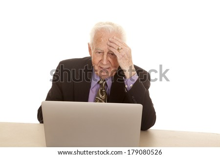 A old man with a computer has his hand on his forehead.