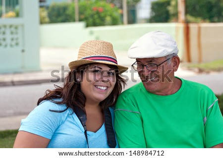 A older Hispanic senior citizen man sits outdoors in a tropical setting with his granddaughter. - stock photo