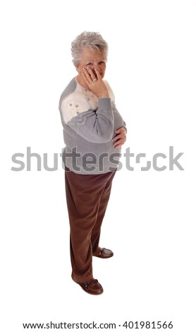 A older senior citizen woman standing isolated for white backgroundholding one hand on her face. - stock photo