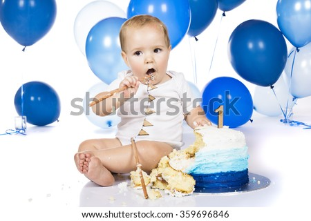 A one year old baby boy smashing a blue iced birthday cake on a silver board with lots of blue helium balloons in the background. - stock photo