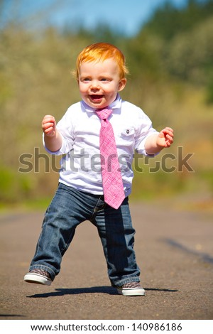 A one year old boy taking some of his first steps outdoors on a path with selective focus while wearing a nice shirt and a necktie. - stock photo