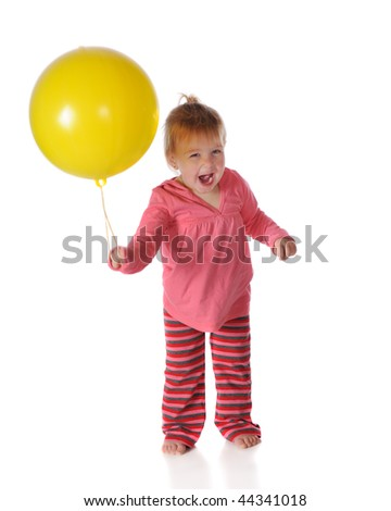 A one-year-old happily playing with a big, yellow punch-ball.  Isolated on white. - stock photo