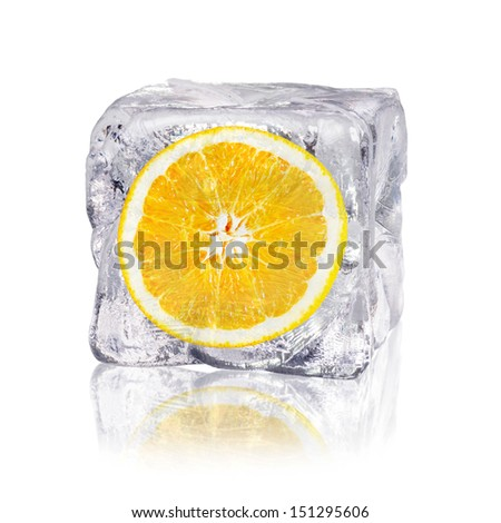 a orange enclosed in an ice cube before white background - stock photo