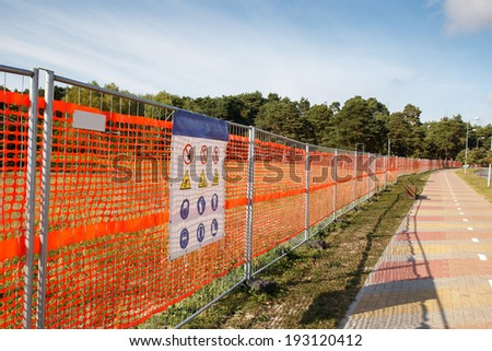 A orange fence with warning signs on it - stock photo