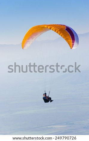 A orange Paraglider is flying in front of mountain - stock photo
