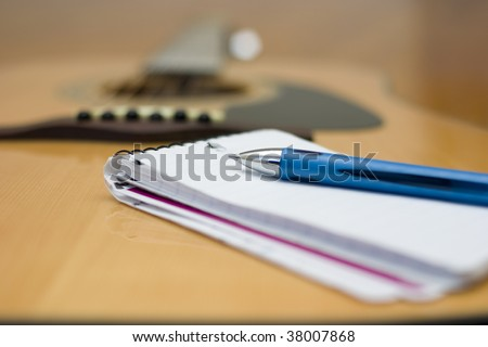 A pad of paper with an acoustic guitar in the background. - stock photo