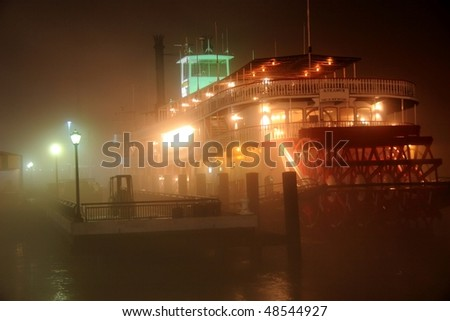 A paddle boat moored on very foggy banks of the Mississippi River in New Orleans, LA - stock photo