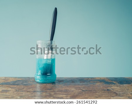A paintbrush is soaking in a jar of blue water - stock photo