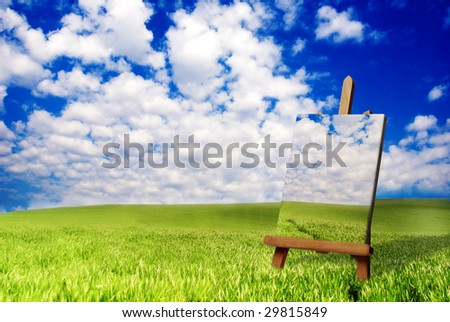 a painter easel in a meadow, with canvas and painting on it - stock photo