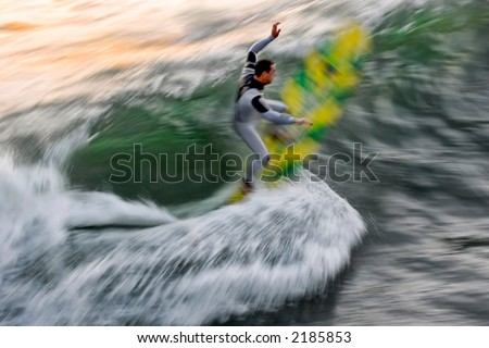 A painterly photo of a surfer at sunset taken with a slow shutter speed to make a creative blur.