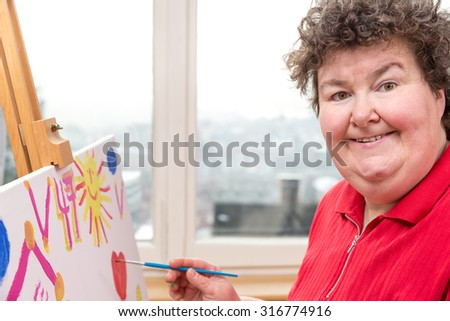 a painting Therapy with a mentally disabled woman - stock photo