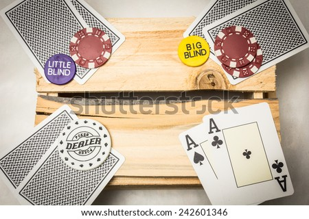 A pair of aces together with a dealer button on a wooden support - stock photo