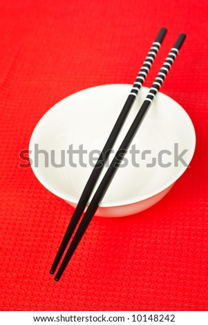 A pair of asian chopsticks and white bowl on the red mat. Shallow DOF - stock photo